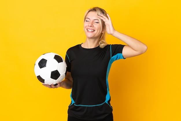 Młoda rosyjska piłkarka odizolowana na żółtym tle dużo się uśmiecha