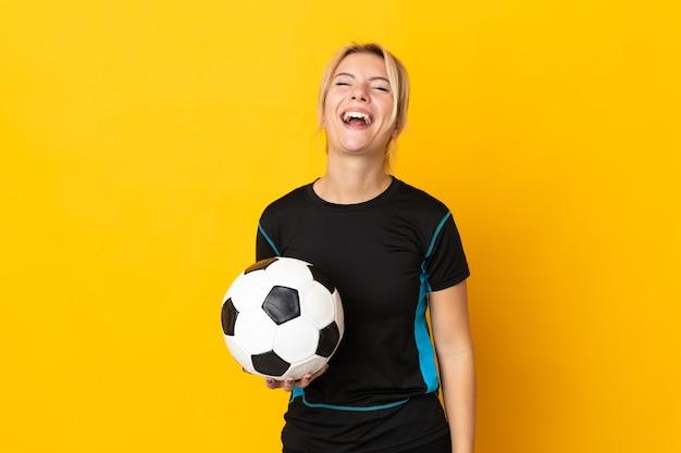 Młoda rosyjska piłkarka odizolowana na żółtym tle śmiejąca się