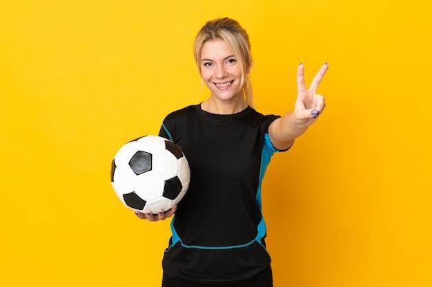 Młoda rosyjska piłkarka odizolowana na żółtym tle uśmiecha się i pokazuje znak zwycięstwa