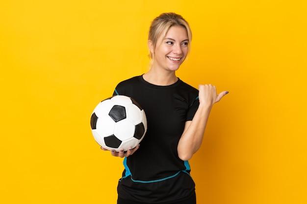 Młoda rosyjska piłkarka odizolowana na żółtym tle wskazująca na bok, aby zaprezentować produkt