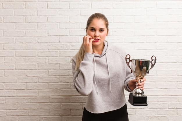 Młoda rosyjska sprawności fizycznej kobieta trzyma trofeum