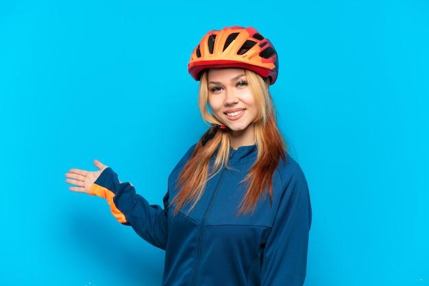 Młoda rowerzysta dziewczyna na białym tle na niebieskim tle wyciągając ręce do boku za zaproszenie do przyjazdu