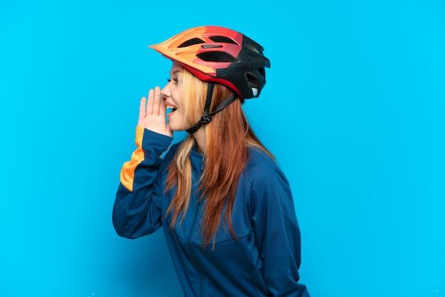 Młoda rowerzystka na białym tle na niebieskim tle krzycząca z szeroko otwartymi ustami