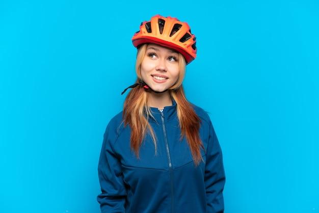 Młoda rowerzystka na białym tle na niebieskim tle myśląca o pomyśle, patrząc w górę