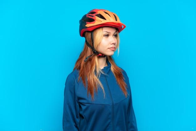Młoda rowerzystka na białym tle na niebieskim tle, patrząc w bok