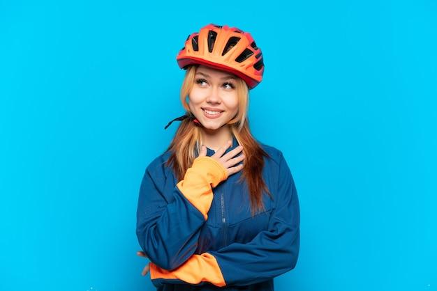 Młoda rowerzystka na białym tle na niebieskim tle patrząc w górę podczas uśmiechania się