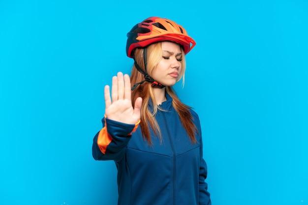 Młoda rowerzystka na białym tle na niebieskim tle robiąca gest zatrzymania i rozczarowana