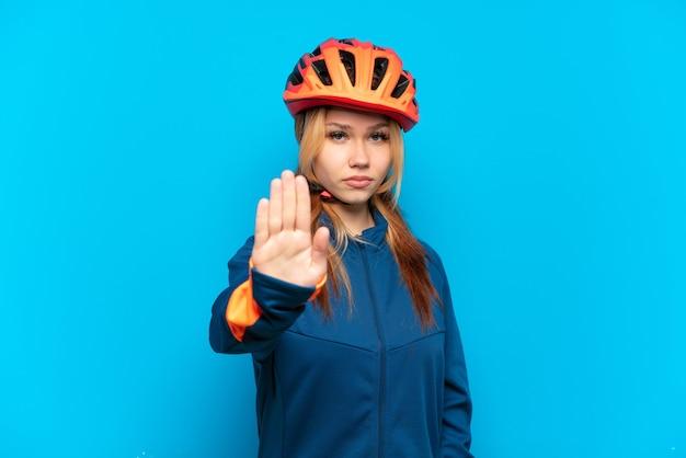 Młoda rowerzystka na białym tle na niebieskim tle robiąca gest zatrzymania