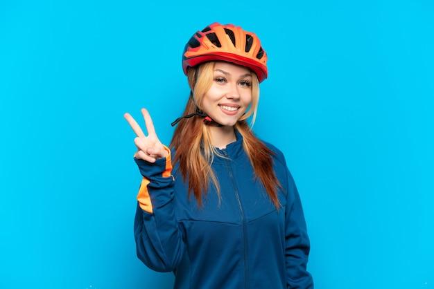 Młoda rowerzystka na białym tle na niebieskim tle, uśmiechając się i pokazując znak zwycięstwa