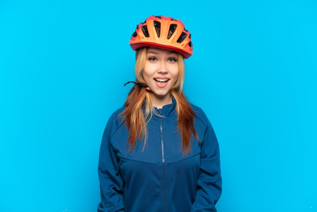 Młoda rowerzystka na białym tle na niebieskim tle z niespodzianką wyrazem twarzy