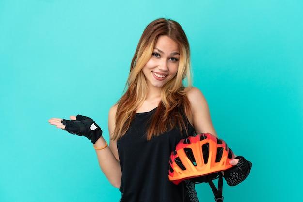 Młoda rowerzystka na odosobnionym niebieskim tle prezentuje pomysł, patrząc w kierunku uśmiechu