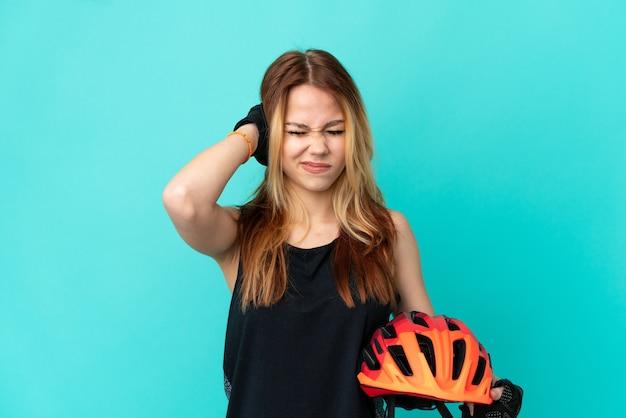 Młoda rowerzystka na odosobnionym niebieskim tle sfrustrowana i zakrywająca uszy