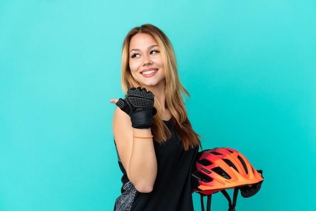 Młoda rowerzystka na odosobnionym niebieskim tle, wskazująca na bok, aby zaprezentować produkt