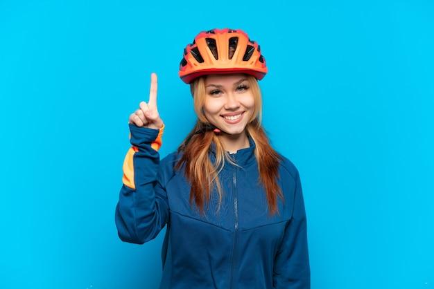 Młoda rowerzystka odizolowana na niebieskim tle wskazująca świetny pomysł