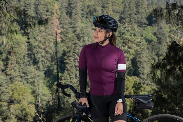 Młoda rowerzystka pozuje na rowerze na punkcie widokowym z zalesionym krajobrazem w tle