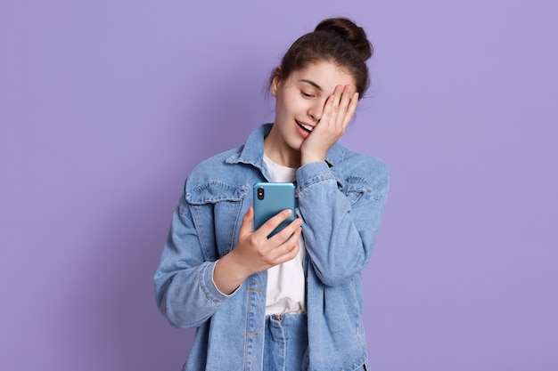 Młoda roześmiana brunetki nastoletnia dziewczyna z włosianą babeczką trzyma mądrze telefon w rękach i zakrywa połówkę twarzy z palmą
