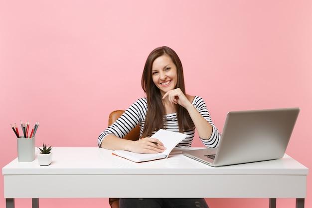 Młoda roześmiana kobieta pisząca notatki na notebooku siedzi przy białym biurku ze współczesnym laptopem pc