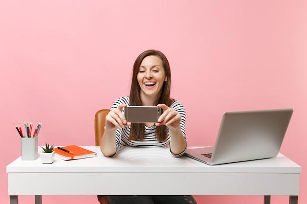 Młoda roześmiana kobieta robi wideorozmowę robi biorąc selfie strzał na telefon komórkowy, podczas gdy siedzieć pracuje przy białym biurku z laptopem pc na białym tle na pastelowym różowym tle. osiągnięcie kariery biznesowej. skopiuj miejsce.