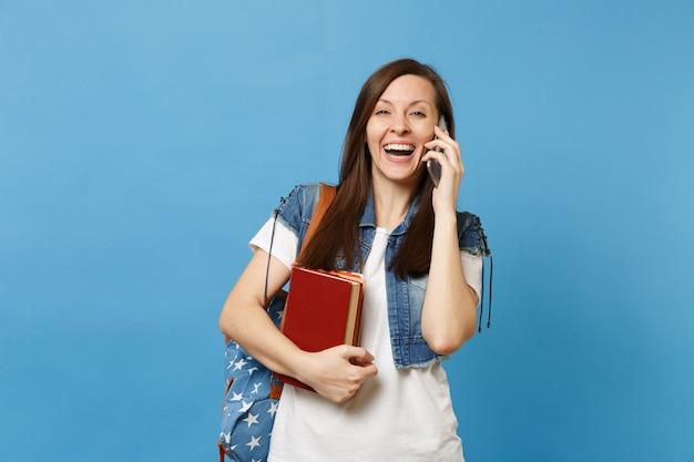 Młoda roześmiana kobieta studentka z plecakiem trzymać podręczniki szkolne rozmowy na telefon komórkowy prowadzenie przyjemnej rozmowy na białym tle na niebieskim tle. edukacja w koncepcji liceum uniwersyteckiego.