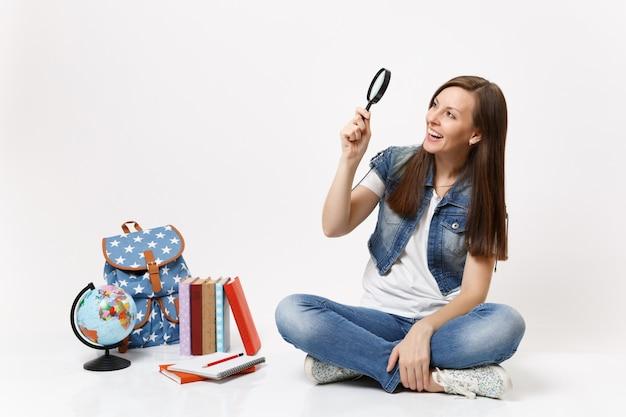 Młoda roześmiana ładna studentka trzyma patrząc na szkło powiększające, siedząc w pobliżu kuli ziemskiej, plecaka, podręczników szkolnych na białym tle