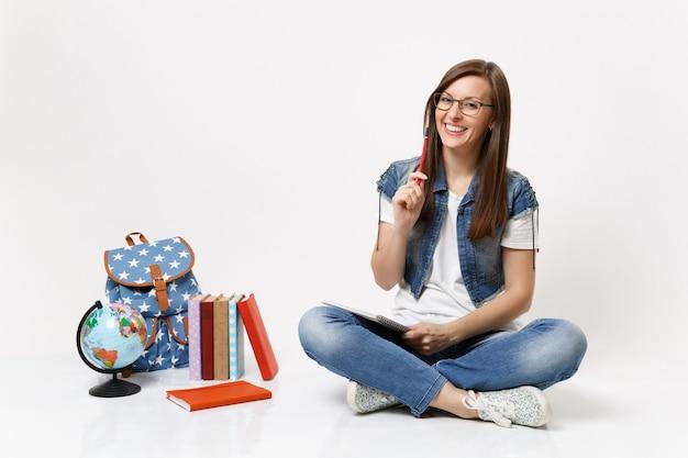 Młoda roześmiana ładna studentka w okularach trzymająca ołówek i notatnik siedząca w pobliżu kuli ziemskiej, plecaka, podręczników szkolnych na białym tle