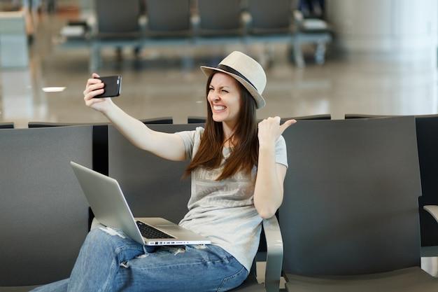 Młoda roześmiana podróżniczka turystyczna kobieta pracuje na laptopie robi selfie na telefonie komórkowym czeka w holu na międzynarodowym lotnisku