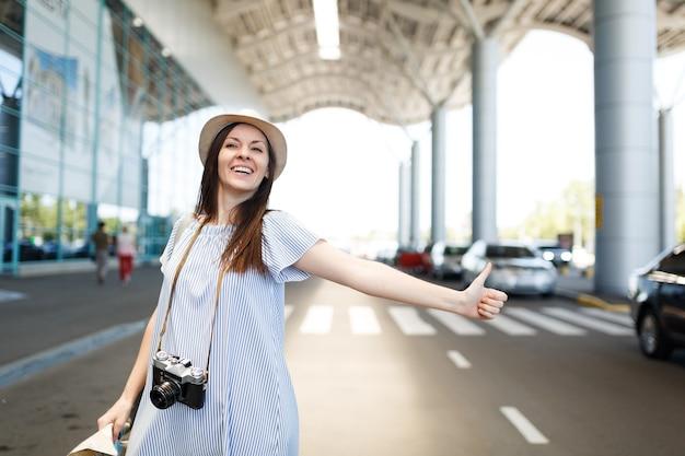 Młoda roześmiana podróżniczka turystyczna kobieta w kapeluszu z retro vintage aparatem fotograficznym trzymająca papierową mapę, łapie taksówkę na międzynarodowym lotnisku