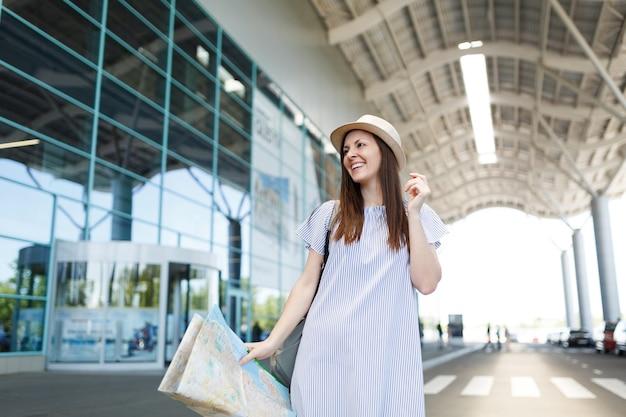 Młoda roześmiana podróżniczka turystyczna kobieta w lekkich ubraniach trzymająca papierową mapę na międzynarodowym lotnisku