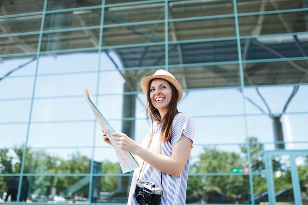 Młoda roześmiana podróżniczka turystyczna kobieta z retro vintage aparatem fotograficznym trzymająca papierową mapę na międzynarodowym lotnisku