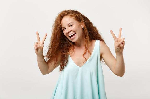 Młoda roześmiana radosna ruda kobieta w dorywczo lekkich ubraniach pozowanie na białym tle na tle białej ściany w studio. koncepcja życia szczere emocje ludzi. makieta miejsca na kopię. wyświetlono znak zwycięstwa.