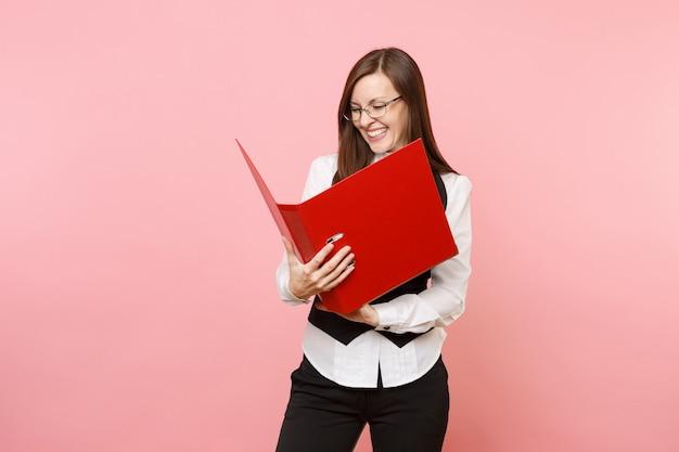 Młoda roześmiana radosna udana kobieta biznesu w okularach patrząc na czerwony folder na dokument dokumentów na białym tle na różowym tle. szefowa. osiągnięcie bogactwa kariery. skopiuj miejsce na reklamę.