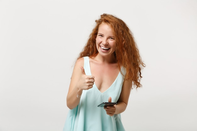 Młoda roześmiana ruda kobieta dziewczyna w dorywczo lekkie ubrania pozowanie na białym tle. koncepcja życia ludzi. makieta miejsca na kopię. używając telefonu komórkowego, wpisując wiadomość sms, pokazując kciuk w górę.