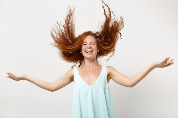 Młoda roześmiana ruda kobieta dziewczyna w dorywczo lekkie ubrania pozowanie na białym tle na białym tle w studio. koncepcja życia ludzi. makieta miejsca na kopię. zabawa, wygłupianie się z rozwianymi włosami.