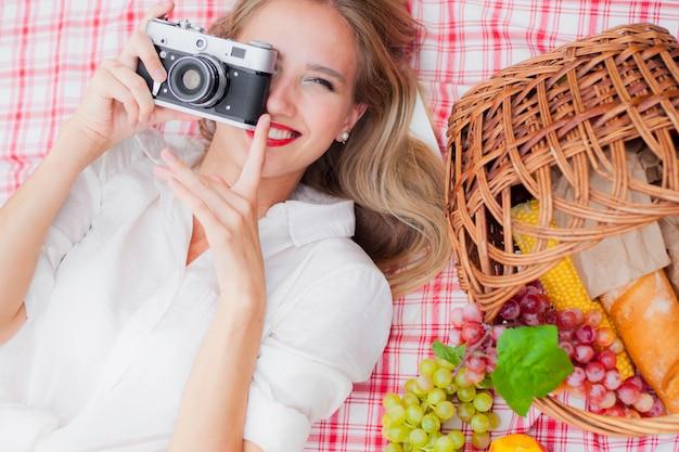 Młoda rozochocona blondynki kobieta w rocznika odzieżowym mieniu retro kamerze i brać fotografię podczas gdy kłamstwa na pyknicznym tablecloth outdoors. widok z góry