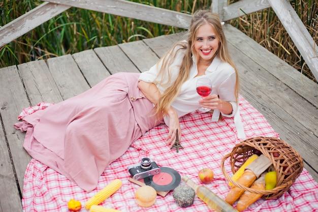 Młoda rozochocona blondynki kobieta w roczników ubraniach pije czerwone wino podczas gdy kłamstwa na pyknicznym obrusie na drewnianym molu