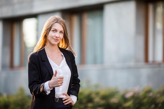 Młoda rozochocona kobieta pokazuje kciuk up
