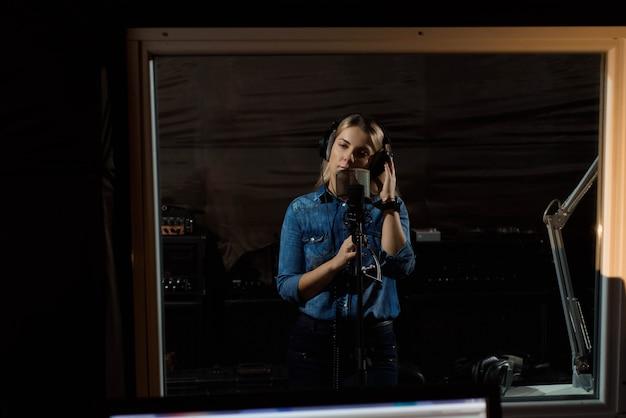 Młoda rozochocona ładna uśmiechnięta blondynki kobieta nagrywa piosenkę
