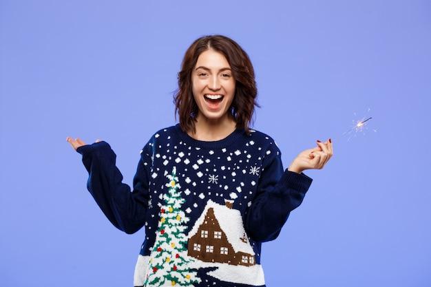 Młoda rozochocona piękna brunetki dziewczyna w przytulnym trykotowym pulowerze uśmiechniętym mieniu bengal zaświeca nad błękit ścianą
