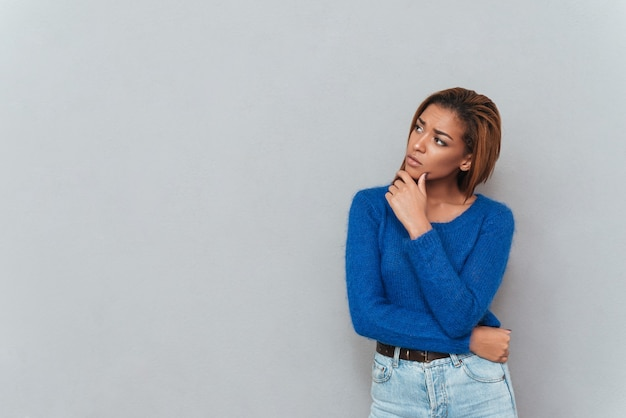 Młoda rozważna afrykańska kobieta w swetrze, patrząc na bok i trzymająca jedną rękę do podbródka.