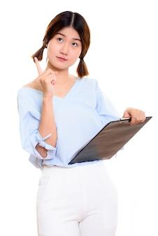 Młoda rozważna azjatycka kobieta wskazując palcem w górę, trzymając schowek