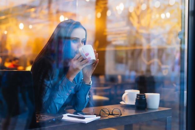 Młoda ruchliwa dziewczyna w niebieskiej koszuli pije pachnącą kawę w kawiarni i wygląda przez okno