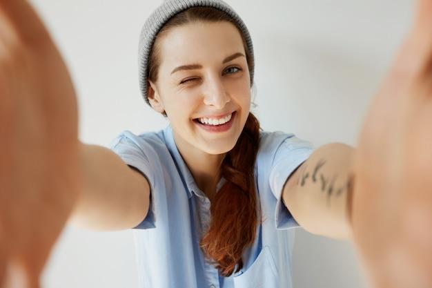 Młoda ruda dziewczyna ma na sobie kapelusz i niebieską koszulę