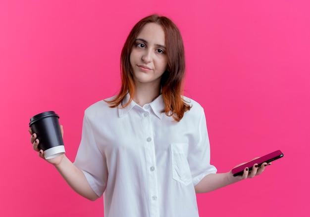 Młoda ruda dziewczyna trzyma telefon i filiżankę kawy na białym tle na różowej ścianie