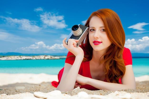 Młoda ruda dziewczyna w czerwonej sukience z aparatem vintage odpoczywa na letniej plaży morskiej