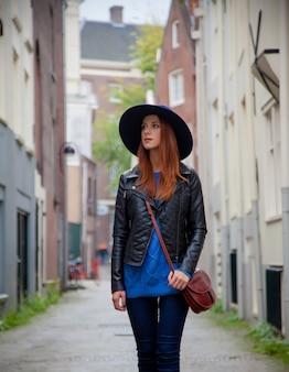 Młoda ruda dziewczyna w kapeluszu na ulicach amsterdamu, holandia