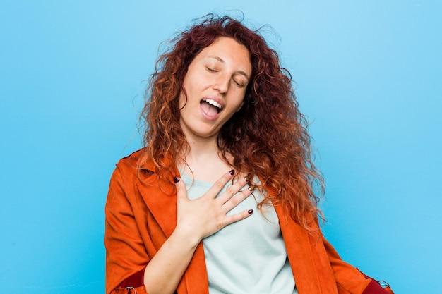 Młoda ruda elegancka kobieta śmieje się głośno, trzymając rękę na piersi.