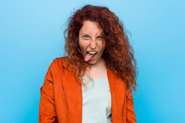 Młoda ruda elegancka kobieta zabawny i przyjazny wystaje język.