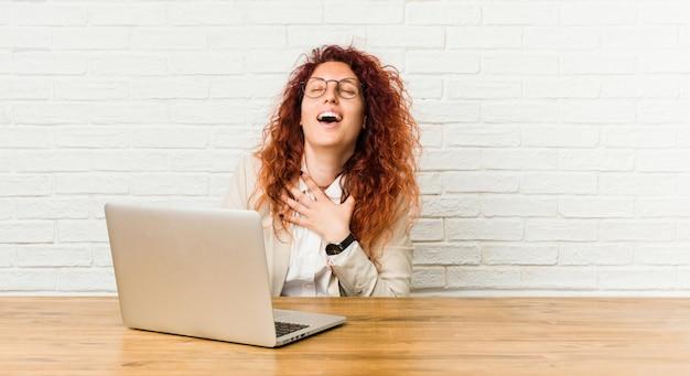 Młoda ruda kędzierzawa kobieta pracująca z jej laptopem śmieje się głośno, trzymając rękę na piersi.