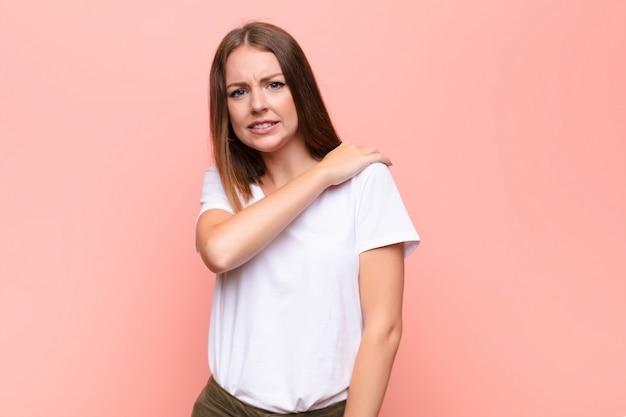 Młoda ruda kobieta czuje się niespokojna, chora, chora i niezadowolona, cierpi na bolesny ból brzucha lub grypę na płaskiej ścianie