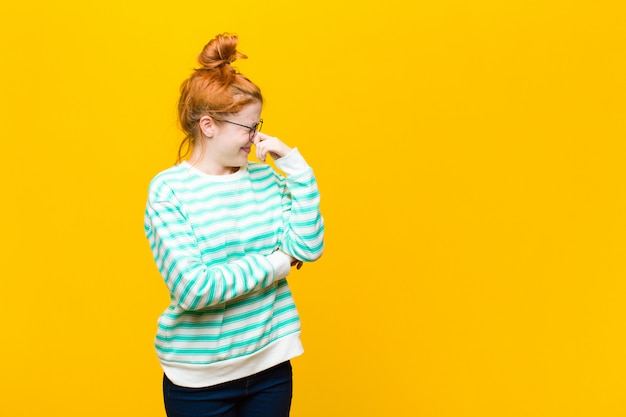Młoda ruda kobieta czuje się zniesmaczona, trzymając nos, aby nie poczuć nieprzyjemnego i nieprzyjemnego smrodu nad pomarańczową ścianą